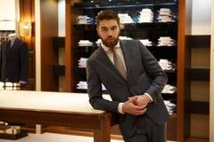 Άτομο στο κοστούμι που στέκεται κοντά στο επιτραπέζιο κατάστημα Στοκ Φωτογραφία