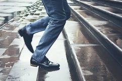 Άτομο στο κοστούμι που τρέχει αργά επάνω στα βήματα στη βροχή Στοκ εικόνες με δικαίωμα ελεύθερης χρήσης