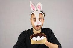 Άτομο στο κουνέλι Πάσχας μασκών που εξετάζει τα αυγά στο καπέλο Στοκ Εικόνες