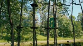 Άτομο στο κράνος και σύστημα ασφάλειας που αναρριχείται στο υψηλό πάρκο σχοινιών περιπέτειας το καλοκαίρι απόθεμα βίντεο