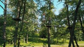 Άτομο στο κράνος στο υψηλό πάρκο σχοινιών περιπέτειας που κάνει τις ασκήσεις στην ενιαία γέφυρα γραμμών απόθεμα βίντεο