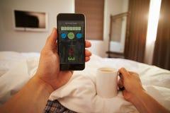 Άτομο στο κρεβάτι που εξετάζει τον έλεγχο υγείας App στο κινητό τηλέφωνο Στοκ εικόνα με δικαίωμα ελεύθερης χρήσης