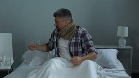 Άτομο στο κρεβάτι που υφίσταται τον επώδυνο λαιμό, που παίρνει το ενάντιο στον ιό φάρμακο, επιδημία γρίπης απόθεμα βίντεο
