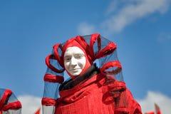 Άτομο στο κόκκινο φανταχτερός-φόρεμα του harlequin Στοκ Εικόνα