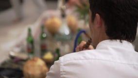 Άτομο στο κόμμα που έχει τη διασκέδαση και που καπνίζει hookah Εορτασμός ενός γάμου, γενεθλίων ή μιας επετείου Γεγονός σε μια πολ απόθεμα βίντεο