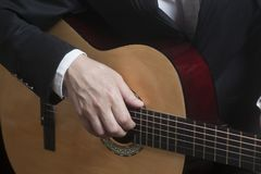 Άτομο στο μαύρο κοστούμι με την ακουστική κλασική κιθάρα Στοκ Φωτογραφία