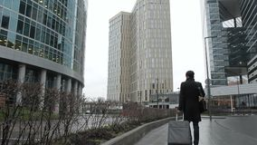 Άτομο στο μαύρο παλτό με τους περιπάτους αποσκευών κατά μήκος της οδού πόλεων με τους ουρανοξύστες φιλμ μικρού μήκους
