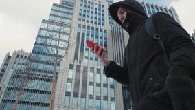 Άτομο στο μαύρο σακάκι και σακίδιο πλάτης χρησιμοποιώντας το κινητό τηλέφωνο και περπατώντας στην οδό πόλεων φιλμ μικρού μήκους