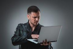 Άτομο στο μαύρο σακάκι που εξετάζει το lap-top, μισή στροφή Κράτημα του ανοιγμένου lap-top και εργασία συγκίνηση Στοκ φωτογραφία με δικαίωμα ελεύθερης χρήσης