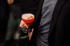 Άτομο στο μαύρο σακάκι που κρατά ένα γυαλί κοκτέιλ με το γλυκό οινοπνευματώδες ποτό Στοκ Εικόνες