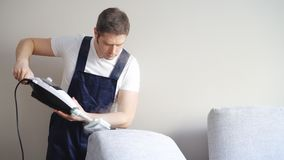 Άτομο στο ομοιόμορφο καθαρίζοντας ύφασμα του καναπέ απόθεμα βίντεο