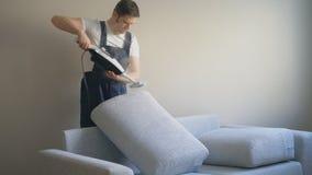 Άτομο στο ομοιόμορφο καθαρίζοντας ύφασμα του καναπέ φιλμ μικρού μήκους