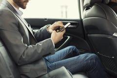 Άτομο στο οπίσθιο τμήμα του αυτοκινήτου Μήνυμα κειμένου δακτυλογράφησης στο κινητό τηλέφωνο Στοκ Φωτογραφίες