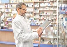 Άτομο στο παλτό εργαστηρίων που λειτουργεί στο φαρμακείο με τα φάρμακα στοκ φωτογραφίες με δικαίωμα ελεύθερης χρήσης