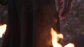 Άτομο στο παλτό με μια κουκούλα στο κεφάλι του που στέκεται στην πυρκαγιά Κάψιμο warlock Κάμερα που κινείται κάτω φιλμ μικρού μήκους