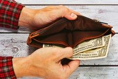 Άτομο στο πορτοφόλι εκμετάλλευσης πουκάμισων εργασίας με ακριβώς δύο δολάρια Στοκ φωτογραφία με δικαίωμα ελεύθερης χρήσης