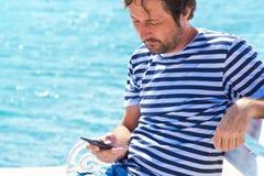 Άτομο στο ριγωτό πουκάμισο ναυτικών που χρησιμοποιεί το κινητό τηλέφωνο εν πλω Στοκ εικόνες με δικαίωμα ελεύθερης χρήσης