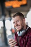 Άτομο στο σιδηροδρομικό σταθμό που χρησιμοποιεί το κινητό τηλέφωνο στην πλατφόρμα Στοκ Εικόνες