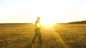 Άτομο στο σκοτεινό κοστούμι με το μαύρο χαρτοφύλακα που περπατά μέσω του τομέα στις ακτίνες ενός φωτεινού ήλιου για μια σημαντική απόθεμα βίντεο
