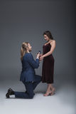 Άτομο στο σμόκιν που κάνει την πρόταση γάμου στη φίλη του στεμένος σε ένα γόνατο Στοκ Εικόνες