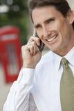 Άτομο στο τηλέφωνο κυττάρων στο Λονδίνο & το κόκκινο τηλεφωνικό κιβώτιο Στοκ φωτογραφία με δικαίωμα ελεύθερης χρήσης