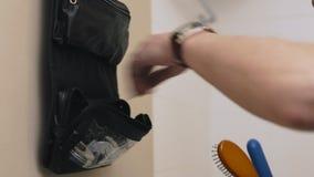 Άτομο συγκομιδών που παίρνει τα εξαρτήματα καλλωπισμού από την τσάντα απόθεμα βίντεο