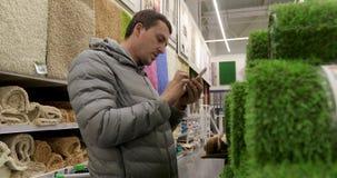 Άτομο συγκομιδών που χρησιμοποιεί το smartphone στην υπεραγορά απόθεμα βίντεο