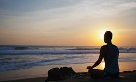 Άτομο συνεδρίασης που κάνει τη γιόγκα στην ακτή του ωκεανού στοκ φωτογραφία