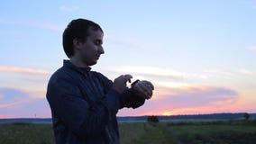 Άτομο σχετικά με το έξυπνο ρολόι στο υπόβαθρο του όμορφου ουρανού ηλιοβασιλέματος απόθεμα βίντεο