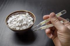 Άτομο, ταμπλέτες φαρμάκων, κύπελλο και ιατρικό θερμόμετρο δύο όπως chopsticks στοκ εικόνες με δικαίωμα ελεύθερης χρήσης