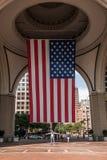 04 09 2017 - άτομο της Βοστώνης Μασαχουσέτη ΗΠΑ που στέκεται κάτω από μια αμερικανική σημαία λωρίδων αστεριών που κρεμά από το θό Στοκ εικόνες με δικαίωμα ελεύθερης χρήσης