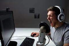 Άτομο τηλεοπτικό παιχνίδι υπολογιστών κασκών στο παίζοντας στο σπίτι Στοκ Εικόνα