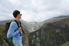 Άτομο τουριστών με ένα σακίδιο πλάτης ενάντια στα βουνά Καύκασου στοκ εικόνες