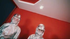 Άτομο τρία στις ασημένιες φόρμες, τα σκληρά καπέλα και τα προστατευτικά δίοπτρα που στέκονται στο κόκκινο δωμάτιο απόθεμα βίντεο