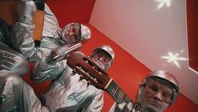 Άτομο τρία στις ασημένιες φόρμες, τα σκληρά καπέλα και τα προστατευτικά δίοπτρα που παίζει τα όργανα μουσικής απόθεμα βίντεο