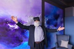 Άτομο τρίτης ηλικίας που βυθίζεται στην εικονική πραγματικότητα με τη βοήθεια ειδικού Στοκ φωτογραφία με δικαίωμα ελεύθερης χρήσης