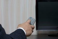 Άτομο χεριών σε ένα κοστούμι με έναν τηλεχειρισμό στη TV Στοκ Φωτογραφίες