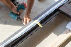 Άτομο χρησιμοποιώντας το κατσαβίδι και κάνοντας μαζί δύο στοιχεία του πλαισίου παραθύρων στοκ φωτογραφία