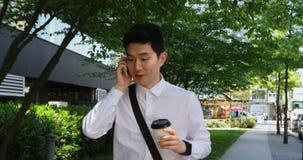 Άτομο χρησιμοποιώντας το κινητό τηλέφωνο και περπατώντας κατά μήκος της οδού 4k φιλμ μικρού μήκους