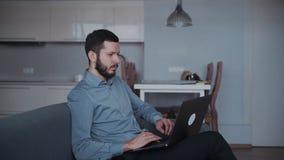 Άτομο χρησιμοποιώντας το σύγχρονο lap-top και καθμένος στον καναπέ στο σπίτι απόθεμα βίντεο