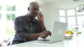 Άτομο χρησιμοποιώντας το lap-top και μιλώντας στο τηλέφωνο στην κουζίνα στο σπίτι απόθεμα βίντεο