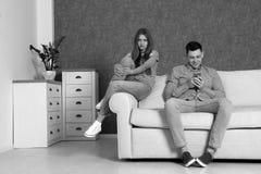 Άτομο χρησιμοποιώντας το smartphone και αγνοώντας τη φίλη του στο δωμάτιο Έννοια μοναξιάς στοκ εικόνες