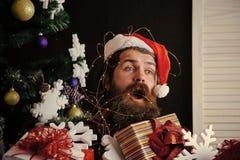 Άτομο Χριστουγέννων με τη γενειάδα στο έκπληκτο πρόσωπο με το παρόν κιβώτιο στοκ εικόνες