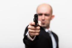 Άτομο όπως τον πράκτορα 007 στο επιχειρησιακό κοστούμι Πυροβόλο όπλο στην εστίαση Άσπρη ανασκόπηση Στοκ εικόνα με δικαίωμα ελεύθερης χρήσης