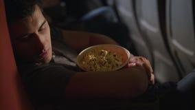 Άτομο ύπνου που αγκαλιάζει popcorn το κιβώτιο στον κινηματογράφο Ύπνος τύπων στην καρέκλα στον κινηματογράφο φιλμ μικρού μήκους