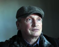 Άτομο ώμων portret περίπου 50 στην γκρίζα ΚΑΠ Στοκ Φωτογραφίες