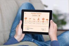 Άτομο app ταμπλετών εκμετάλλευσης καναπέδων στην καταδίωξη συσκευασίας στην οθόνη Στοκ Φωτογραφίες
