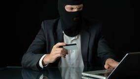 Άτομο balaclava και κοστούμι που δεσμεύει την απάτη τραπεζών, που χρησιμοποιεί την κλεμμένη πιστωτική κάρτα, έγκλημα απόθεμα βίντεο