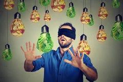 Άτομο Blindfolded που περπατά μέσω των λαμπών φωτός που διαμορφώνονται ως άχρηστο φαγητό και πράσινα λαχανικά Στοκ εικόνες με δικαίωμα ελεύθερης χρήσης