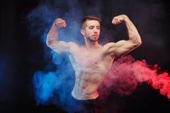 Άτομο Bodybuilder με τους τέλειους μυς στον μπλε και κόκκινο καπνό Στοκ Φωτογραφία
